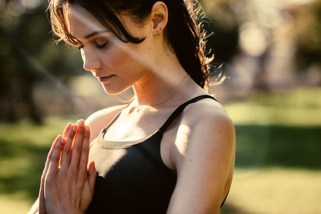 Fitness woman meditating at the park in morning