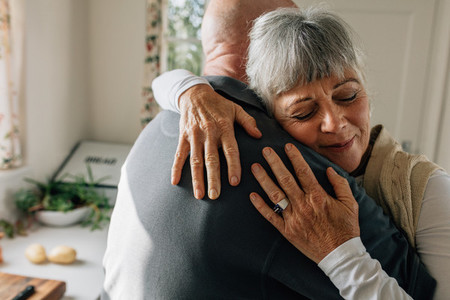 Senior couple hugging each other at home
