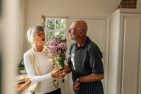 Senior man giving a bouquet to his wife