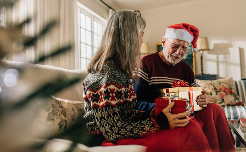 Senior couple exchanging christmas gifts sitting at home