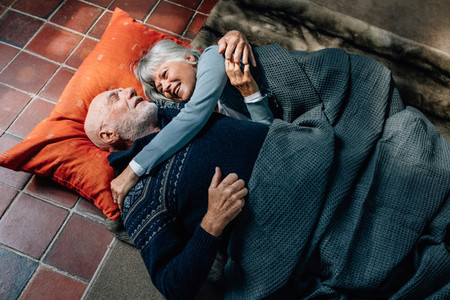 Senior couple sleeping together on floor