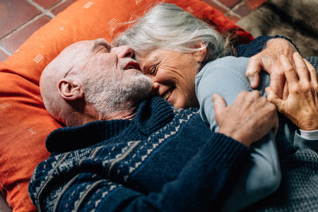 Senior couple lying on floor embracing each other