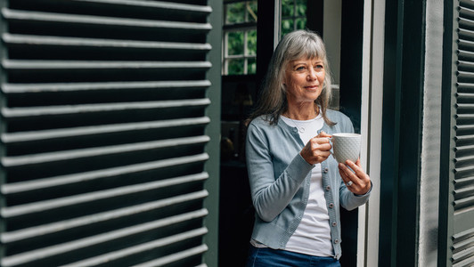 Senior woman standing at the door holding a coffee cup