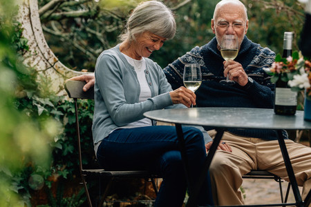 Old couple enjoying a glass of wine sitting together