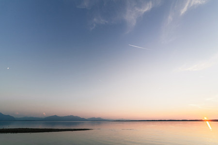 Sunset ion a bavarian lake with moon and sun at the same time