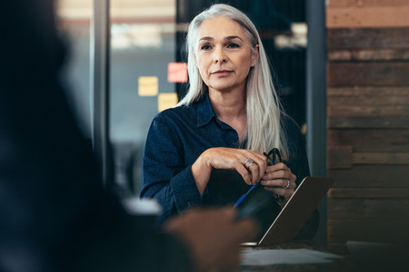 Senior business woman sitting in meeting at office