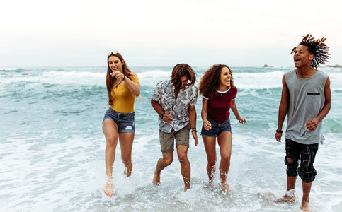 Cheerful young friends walking out of sea water