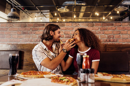 Smiling couple feeding each other pizza