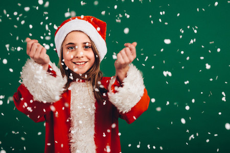 Girl in santa claus dress enjoying artificial snowfall