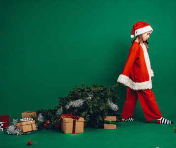 Little girl walking away with a christmas tree
