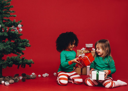 Little girls playing with their christmas gifts boxes