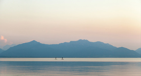 A couple practicing paddlesurf at sunset on a lake