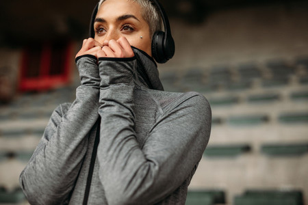 Woman in sweatshirt standing in a stadium listening to music
