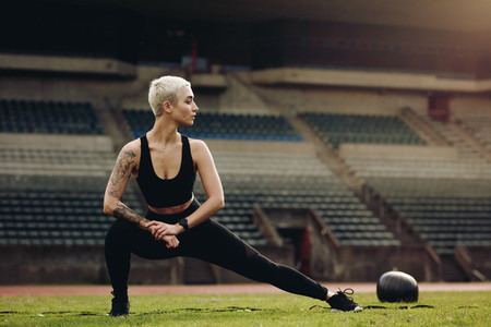 Woman athlete doing stretching exercises in a stadium