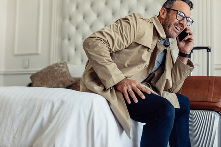Successful businessman in hotel room talking on mobile phone