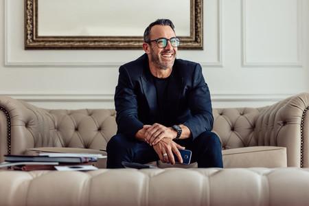 Happy mature businessman sitting in hotel room