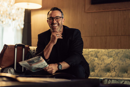 Happy mature businessman waiting in hotel lobby