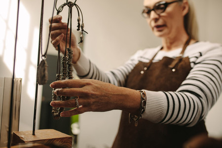 Mature female jeweler hanging a necklace on stand