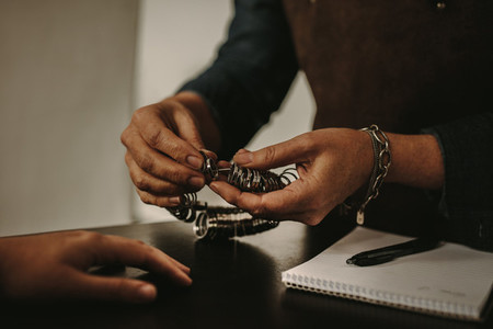 Jewelry designer checking clients finger size