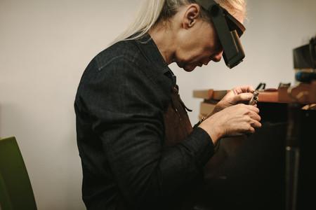 Senior female jeweler making new product