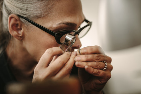 Mature female jeweler looking at stone through loupe