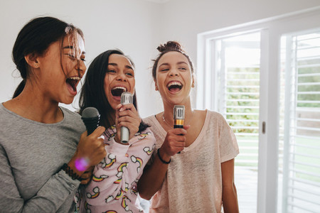 Girls singing karaoke at a sleepover