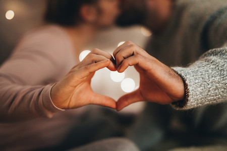 Close up of hands of a couple making a heart shape