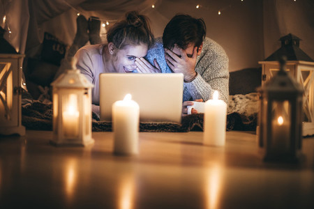 Couple enjoying a movie at night in bedroom