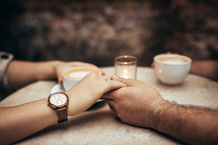 Close up of hands of a couple in love at a coffee shop