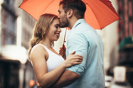 Romantic couple standing under an umbrella in street