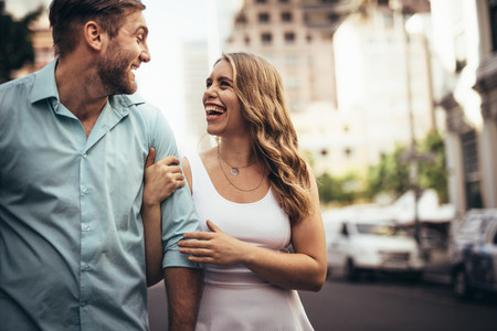 Couple walking on street holding hands and talking