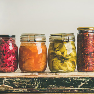 Autumn pickled colorful vegetables in jars placed in row