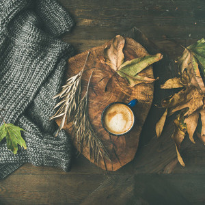 Autumn coffee concept with leaves and grey sweater square crop