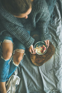 Woman in sweater and jeans eating rice coconut porridge