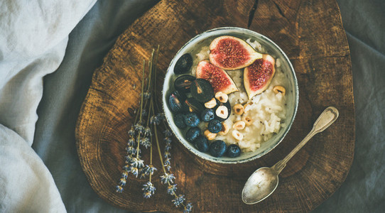 Rice coconut porridge with figs berries and hazelnuts in bowl