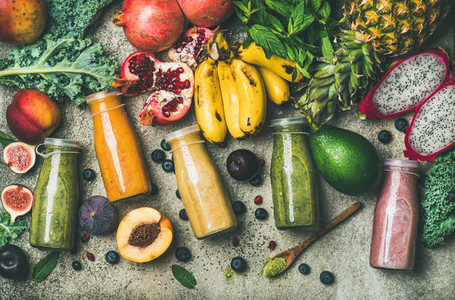 Colorful smoothies in bottles with fresh tropical fruit and superfoods