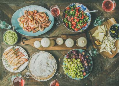Flat lay of salad  shrimps  olive  grape  cake over wooden background