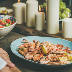 Salad  shrimps and candles on wooden table  square crop
