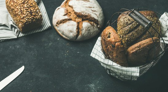 Various bread loaves over black background  copy space  horizontal composition