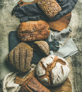 Flat lay of various bread loaves on grey background  top view