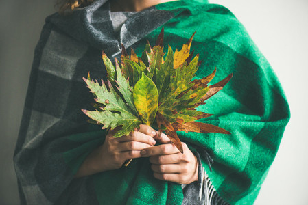 Woman in warm scarf holding Autumn leaves