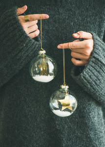 Woman in grey warm woolen sweater holding toy glass balls