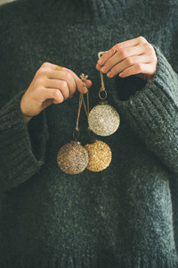Woman in grey sweater holding golden and silver balls