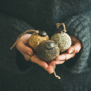 Woman holding golden and silver toy balls in hands