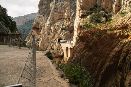 A train crossing a tunnel between hills over a stone bridge
