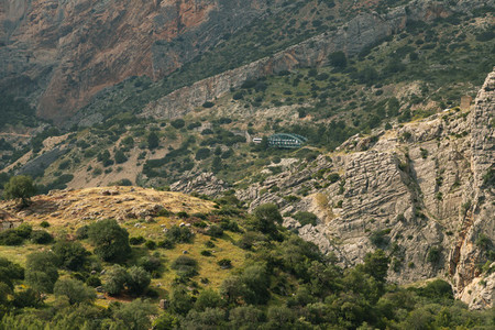 Breathtaking views of a large valley in Ardales  Andalusia  with a hut illuminated by the sun and a train crossing a tunnel