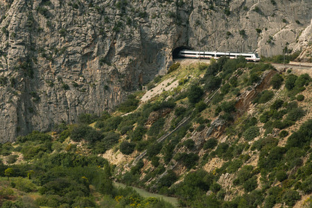 Train crossing a tunnel in a large valley in ardales  andalusia surrounded by hills