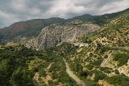 Train approaching a tunnel in a large valley in ardales  andalucia  surrounded by hills and a river