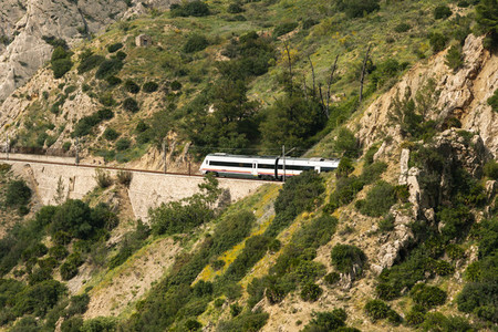 Train crossing a tunnel in a large valley in ardales  andalucia  surrounded by hills