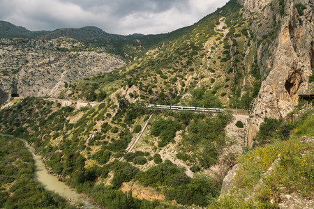 Train crossing a tunnel in a large valley in ardales  andalucia  surrounded by hills and a river